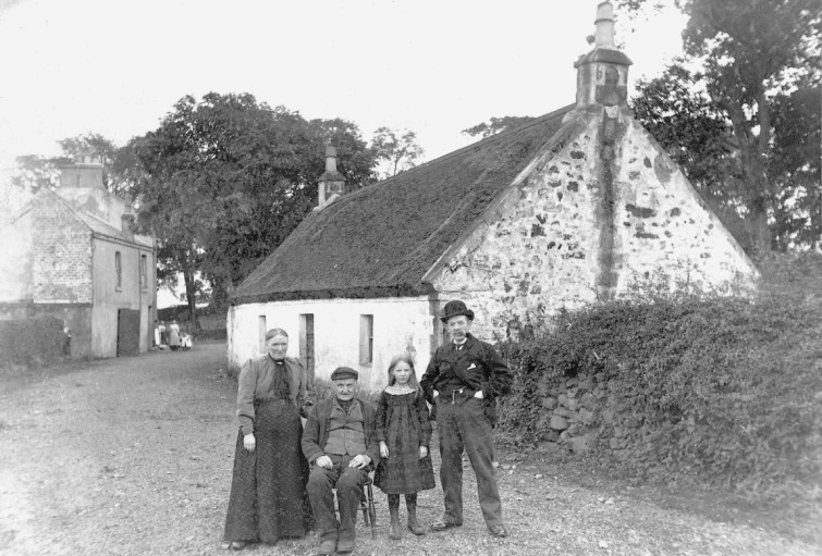 David Arthur (right), Beadle of Mearns Kirk, with his family outside the Thatchit Cottage at Mearnskirk Late 19th century