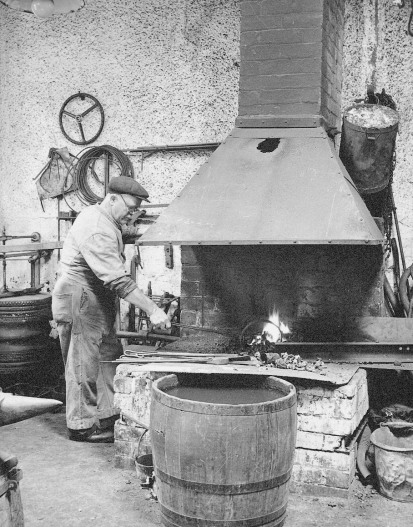 Robert Cottman at his forge in Andersons Garage. He made replacement spares for cars.